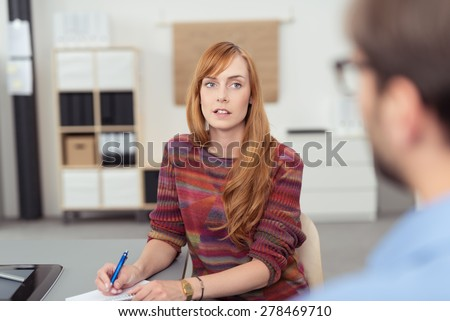 Attractive young redhead businesswoman sitting at her desk taking notes and listening to a colleague, view over his shoulder - stock photo