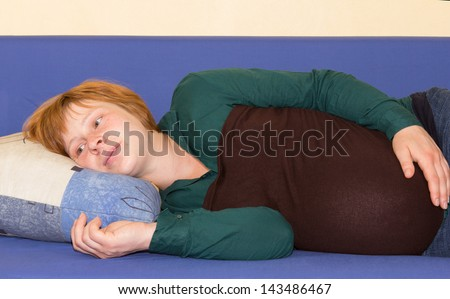 Attractive young redhead pregnant woman lying on a sofa on her side hold her belly with her head on a cushion staring into space thinking and waiting for the birth of her child