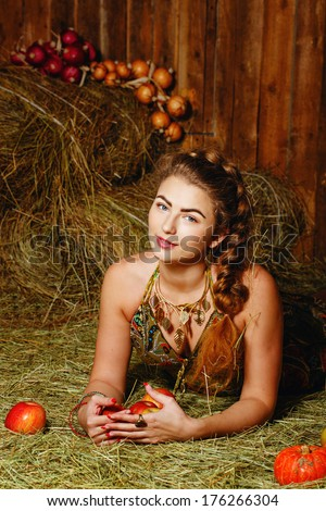 Attractive young rural girl in the hayloft after harvest festival