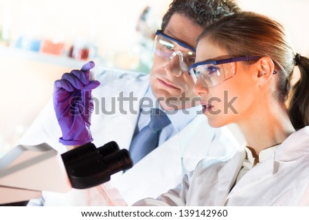 Attractive young scientist and her suprvisor looking at the microscope slide in the forensic laboratory. - stock photo