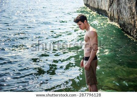 Attractive young shirtless athletic muscle man standing in water by sea or ocean shore, wearing shorts, showing muscular body - stock photo
