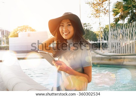 Attractive young smiley Asian businesswoman uses modern tablet outside the office. portrait of a beautiful Asian female students recorded a video for her video blog - stock photo