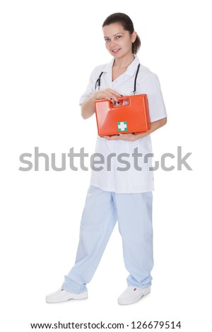 Attractive young smiling female nurse or doctor carrying a portable first aid kit isolated on white - stock photo