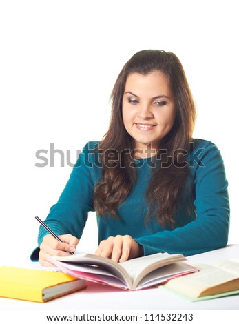 Attractive young smiling girl in a blue shirt sitting at the table and wrote a note of colorful books. Isolated on white background