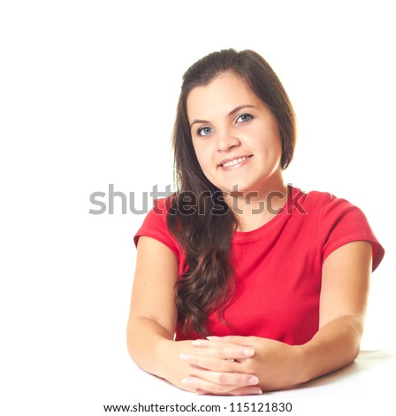 Attractive young smiling girl in a red shirt sitting at the table with folded hands. Isolated on white background