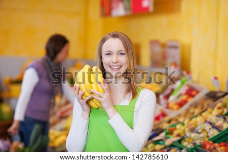 Attractive young smiling shop assistant holding a bunch of ripe bananas in her hands in front of the fresh fruit display - stock photo