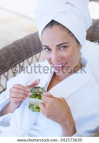 Attractive young smiling woman drink green tea - stock photo