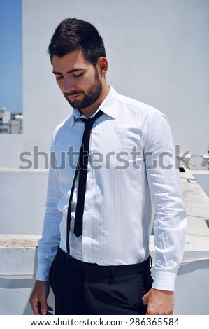 Attractive young Spanish looking man with a beard and dark hair and eyes wearing a classy white shirt and a black tie. - stock photo