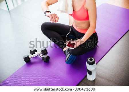 Attractive young sportswoman sitting and using fitness tracker and smartphone on mat in gym - stock photo