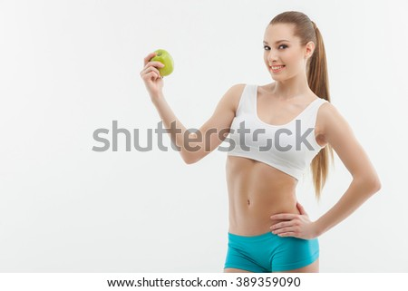 Attractive young sportswoman with a green fruit - stock photo