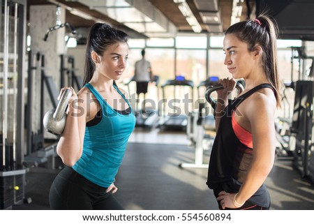 Attractive young sporty girls exercising with kettlebells in a gym.