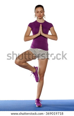 Attractive young sporty woman standing in yoga pose - stock photo