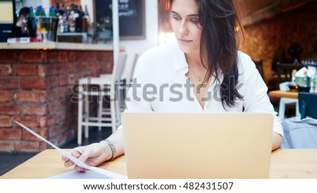 Attractive young student is looking at the documents while sitting in a coffee-shop with a laptop. A beautiful modern female businesswoman wearing white shirt is sitting behind a portable computer.