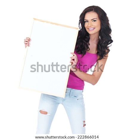 Attractive young student with long brunette hair in trendy jeans holding a blank white sign with copyspace for your text - stock photo