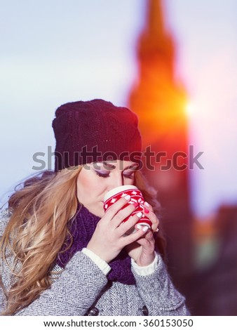 Attractive young stylish blonde girl drinks hot drink from a mug outdoor on a cold winter day - stock photo