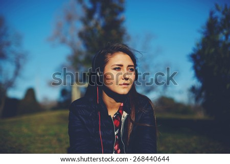 Attractive young teen wearing headphones and listening to music outdoors, pretty girl relaxing and listening to music - stock photo