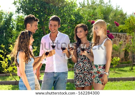 Attractive young teenagers partying outdoors standing in a group on the lawn in the garden in the summer sun enjoying a glass of red wine together - stock photo