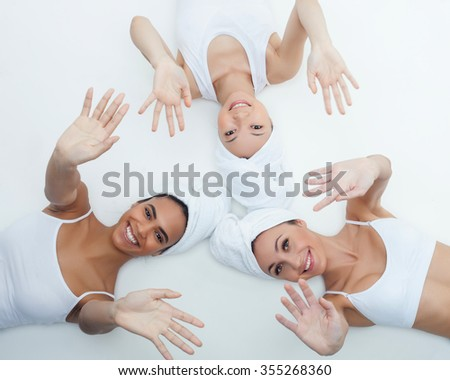 Attractive young three women are lying with white towels on their heads. They are stretching arms up and smiling. The girls are looking at camera happily. Isolated - stock photo