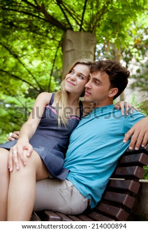 Attractive young tourist couple sitting down on a  wooden bench while visiting a green garden park on a weekend city travel break. Loving girlfriend and boyfriend enjoying a summer day outdoors. - stock photo