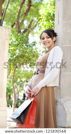 Attractive young tourist woman holding her shopping bags while leaning on a column in a romantic garden, outdoors. - stock photo