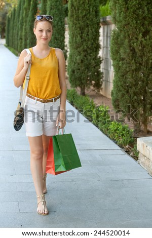 Attractive young tourist woman walking on pavement by a green park in a destination city carrying shopping bags during sunny summer holiday trip, enjoying and smiling. Travel and lifestyle outdoors.