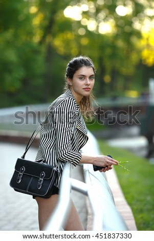 Attractive young trendy dressed woman enjoying her time outside in park with sunset in foliage