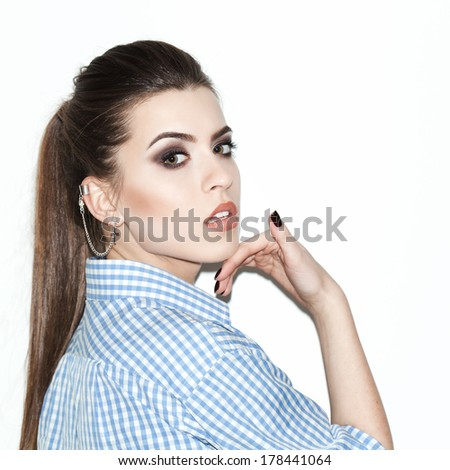 Attractive young trendy  girl posing by the wall. Not isolated. Indoor - stock photo