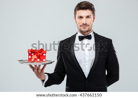 Attractive young waiter in tuxedo with bowtie holding present box on tray - stock photo