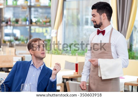 Attractive young waiter is receiving an order. He is standing and smiling. The businessman is sitting at the table and talking. The woman is looking at the waiter with joy - stock photo