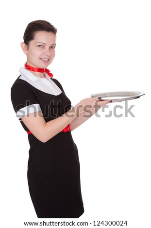 Attractive young waitress in a smart uniform holding an empty service tray out in front of her - stock photo