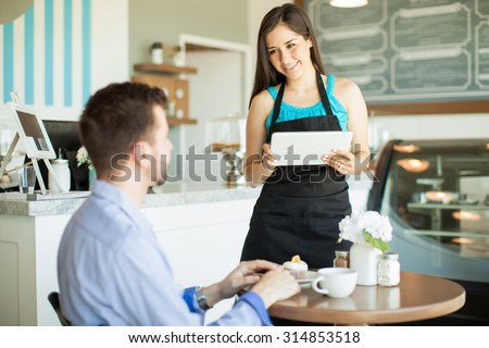 Attractive young waitress using a tablet computer to take an order from a customer in a coffee shop - stock photo