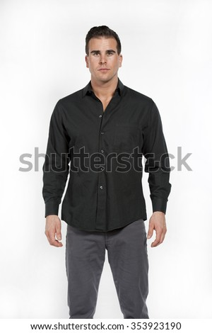 Attractive young white caucasian male model wearing a black formal shirt and gray pants posing in a studio on a white background while looking at the camera. - stock photo