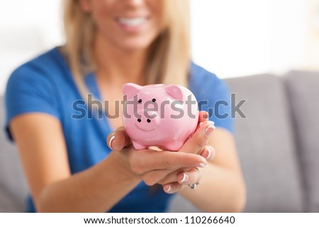 Attractive young white female with beautiful long blond hair holding cute pink piggy bank.