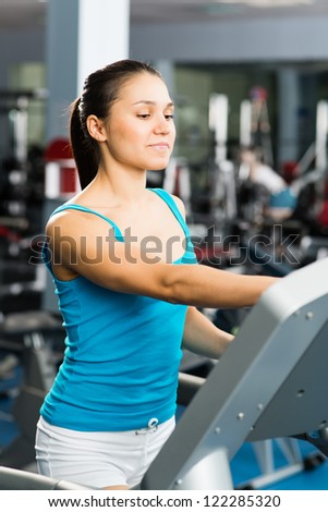 attractive young woman adjusts the treadmill at the beginning of training, do fitness in the sport club - stock photo