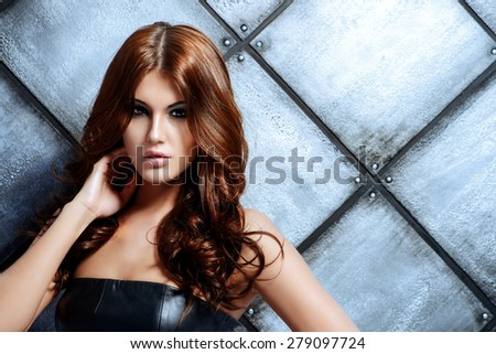 Attractive young woman alluring in black dress by the grunge metallic background. Studio shot. Beauty, fashion. - stock photo