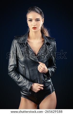 Attractive young woman alluring in fitting leather suit. Beauty, fashion. - stock photo