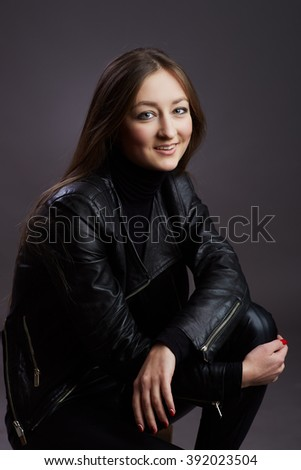 Attractive young woman alluring in fitting leather suit. Beauty, fashion - stock photo