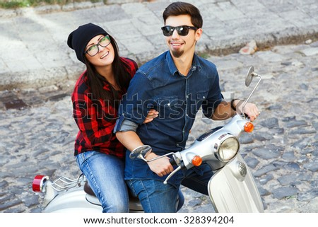 Attractive young woman and man wearing on glasses, shirts and jeans, sitting on a vintage scooter on the street of old European city, waist up