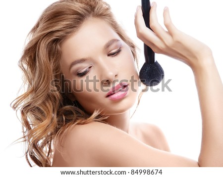 Attractive young woman applying makeup powder on white background, caucasian woman makeup