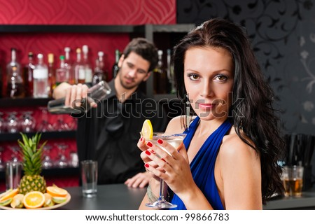 Attractive young woman at cocktail bar enjoy drink from bartender