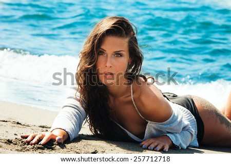attractive young woman at sandy beach by the blue sea water, lie down looking at camera, hot summer day - stock photo