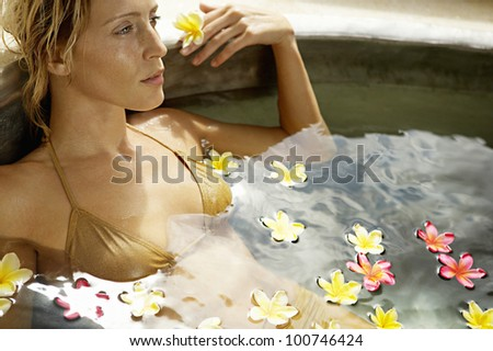 Attractive young woman bathing in a bath of flowers in a health spa. - stock photo