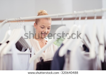 Attractive Young Woman Behind Clothing Rail Looking for Clothes Inside Fashion Store. - stock photo