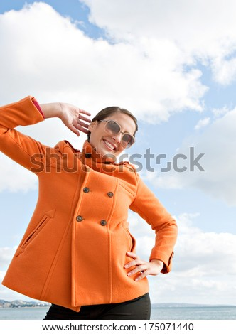Attractive young woman being playful and posing with her orange coat being fun and quirky against a sunny blue sky with white clouds by the sea. Outdoors lifestyle coastal portrait. - stock photo