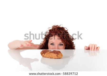 Attractive young woman being tempted, ready to take the éclair from table. Studio shot. White background. shallow dof, focus on eyes - stock photo