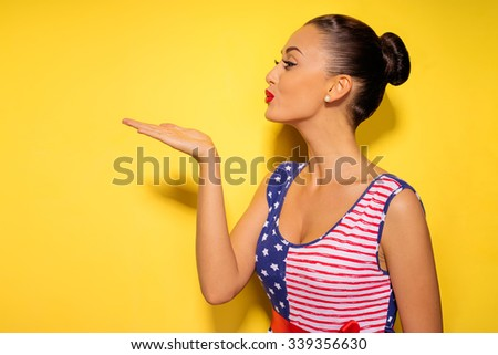 Attractive young woman blowing kiss away. Yellow background. - stock photo