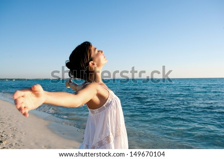 Attractive young woman breathing fresh air while standing on a beach shore with her arms outstretched back, enjoying the intense blue sea and sky at sunset during a vacation.