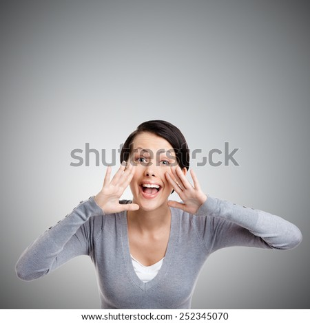 Attractive young woman calls for somebody, isolated on grey - stock photo
