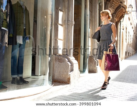 Attractive young woman carrying shopping bags walking in city with fashion stores, joyfully smiling and looking at shop windows, sunny outdoors. Consumer girl, exclusive expensive lifestyle exterior.