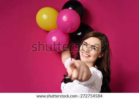 Attractive young woman celebrating with a bunch of colorful balloons laughing and pointing at the camera with her finger, focus to her face - stock photo